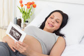 Pregnant woman looking at sonography report — Stock Photo