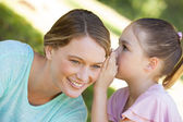 Girl whispering secret into mother's ear at park — Foto Stock