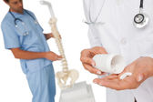 Mid section of female doctor with pills and skeleton model — Stock Photo