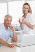 Happy couple using laptop together at the counter — Stock Photo