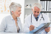 Male doctor explaining x-ray report to senior patient — Stock Photo