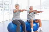 Senior couple doing stretching exercises on fitness balls — Stock Photo