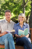 Couple holding books in park — Stock Photo