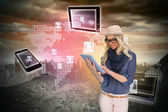 Stylish blonde using tablet pc with connecting devices — Stock Photo