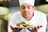 Closeup of a chef with eyes closed smelling food — Stock Photo