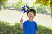 Happy cute little boy holding pinwheel at park — Stock Photo