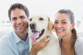 Happy couple rubbing their yellow labrador on the couch — Stock Photo