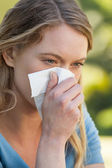 Woman blowing nose with tissue paper at park — Stock Photo