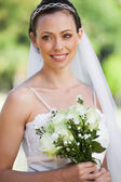 Smiling young beautiful bride with bouquet in park — Stock Photo