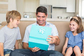 Father opening gift given by children — Stock Photo