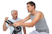 Determined young man on stationary bike with trainer — Stok fotoğraf