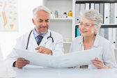 Doctor with female patient reading reports — Stock Photo