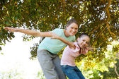 Portrait of mother and daughter with arms outstretched at park — ストック写真