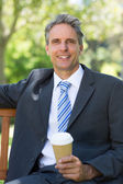 Businessman with disposable coffee cup — Stock Photo