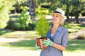 Woman looking at potted plant in garden — Stock Photo