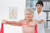 Physiotherapist massaging senior womans back — Stock Photo