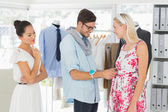 Fashion designer adjusting dress on model — Stock Photo