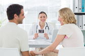 Gynaecologist looking at expectant couple — Stock Photo