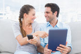 Smiling couple sitting on the couch using tablet pc and watching tv — Stock Photo