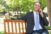 Businessman with disposable cup answering cellphone  — Stock Photo