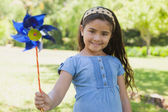 Cute little girl holding pinwheel at park — Stock Photo