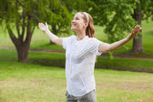 Woman with arms outstretched at park — Stockfoto
