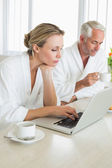 Couple having coffee at breakfast in bathrobes using laptop — Stock Photo