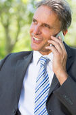 Businessman answering smartphone — Stock Photo