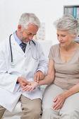 Male doctor taking a senior females pulse — Fotografia Stock