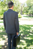 Businessman carrying briefcase in park — Stock Photo