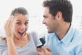 Delighted young couple getting engaged on the sofa — ストック写真