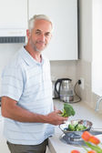 Casual man rinsing broccoli in colander and smiling at camera — Stock Photo