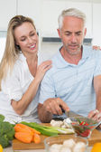 Affectionate couple preparing dinner together — Stock Photo