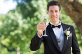 Groom holding champagne flute — Stock Photo