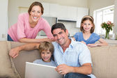 Family using laptop in sitting room — Stock Photo