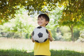 Happy cute little boy with football at park — Stock Photo