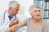 Male doctor injecting senior patient — Stock Photo