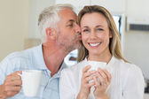 Casual man giving his smiling partner a kiss on the cheek — Stock Photo