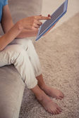 Low section of a young woman using digital tablet — Stock Photo