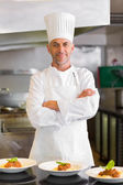 Confident male chef with cooked food in kitchen — Stock Photo