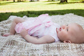 Side view of a cute baby lying on blanket at park — Stock Photo