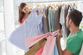 Man with shopping bags while woman selecting a dress — Stock Photo