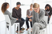 Upset woman with head in hands at rehab group — Stock Photo