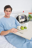 Man in gown having mean in hospital — Stock Photo