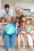 Family exploring globe in living room — Stock Photo