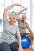Senior couple doing stretching exercises on fitness balls — Stock Photo