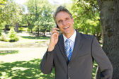 Businessman answering smart phone  — Stock Photo