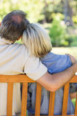 Couple relaxing on bench in park — Stock Photo