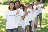 Volunteers gesturing thumbs up in park — Stock Photo