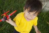 Jongen speelt met een vliegtuig speelgoed in het park — Stockfoto